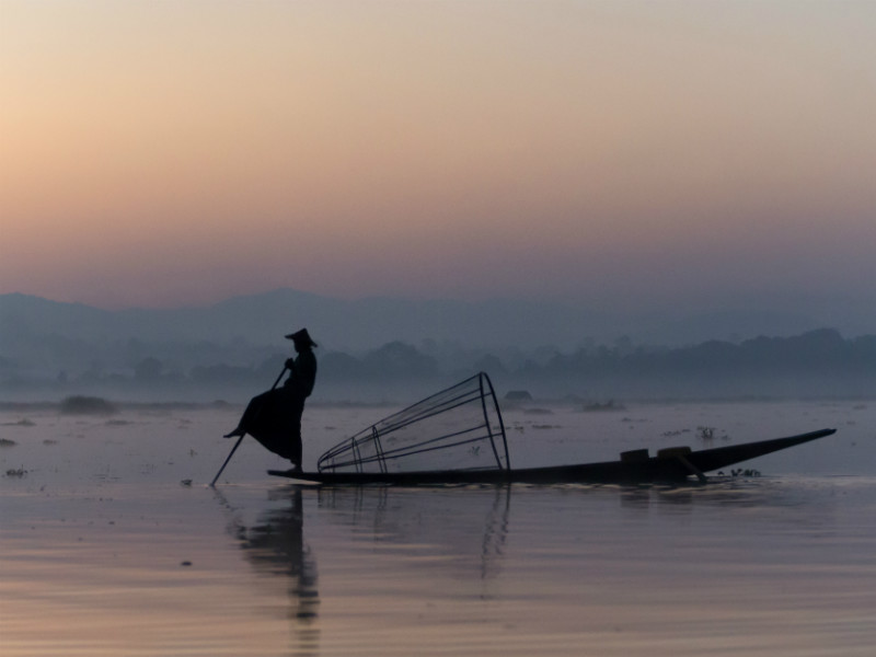 Fisherman rowing at dusk