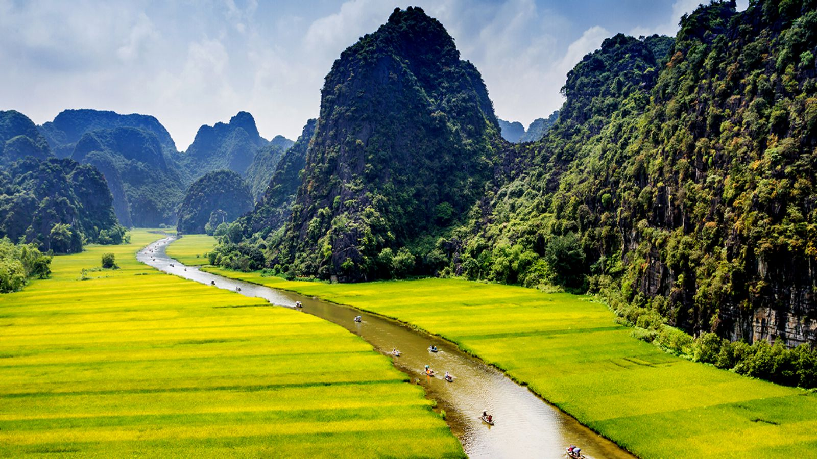 Brilliant colors of yellow rice fields, green forests, and white soft cloud of Trang An make this place surreal and spectacular
