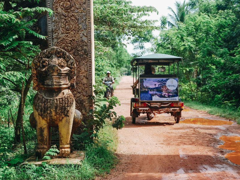 A tuk-tuk is on a dirt road. The life in Kep still keeps quiet and private